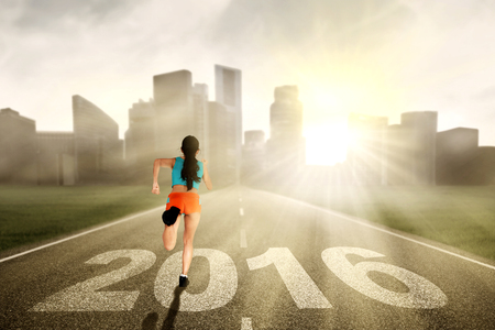 overtake: Image of young healthy woman wearing sportswear and running on the road with numbers 2016 Stock Photo