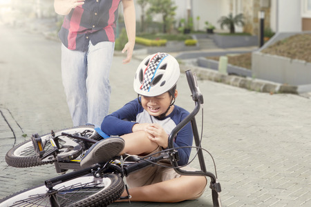people street: Portrait of little boy crying while holding his knee after falling from the bike with father coming for help