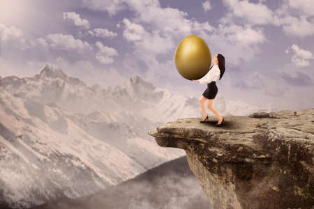 has: Businesswoman has gold egg investment on top of a mountain Stock Photo
