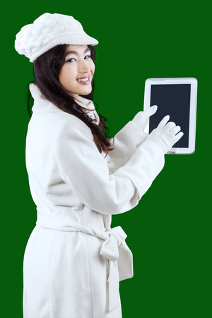 green clothes: Cheerful young woman wearing winter clothes and smiling at the camera while using a digital tablet computer with green background Stock Photo