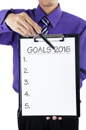 metas: Foto del hombre de negocios que sostiene un sujetapapeles y que muestra el n�mero de listas para hacer plan o metas en 2016