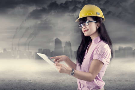 contaminacion aire: Ingeniero de sexo femenino que usa la tableta digital, al aire libre. disparar bajo la contaminación del aire Foto de archivo