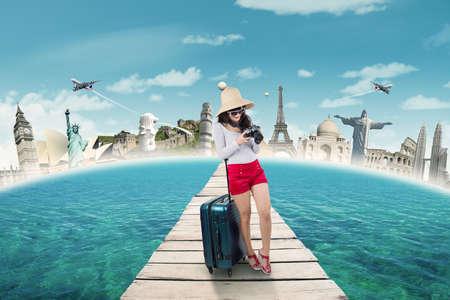 여행: 세계 기념물에 휴가를 가방과 카메라를 들고있는 동안 다리에 서있는 젊은 여자