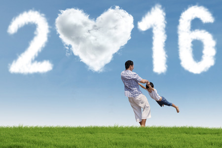 new years vacation: Image of young father playing on the meadow with his son under cloud shaped numbers 2016
