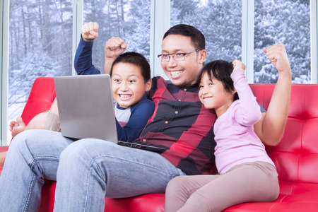 excited: Image of excited children and their father sitting on the sofa while using laptop computer and raise hands