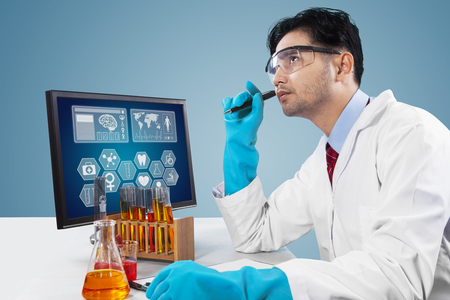 estudiantes medicina: Científico de sexo masculino que trabaja en el laboratorio con el líquido químico y piensa en el descubrimiento Foto de archivo