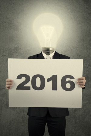 new years resolution: Image of businessman with lightbulb head holding poster with numbers 2016
