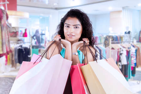 carrying girl: Beautiful indian woman with curly hair, holding shopping bags at shopping center