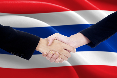 campaigning: Image of two politicians in formal suit, shaking hands in front of Thailand national flag Stock Photo