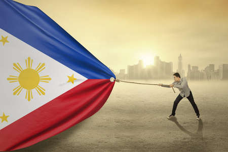 happy workers: Photo of young person with casual clothes pulling Philippines national flag Stock Photo