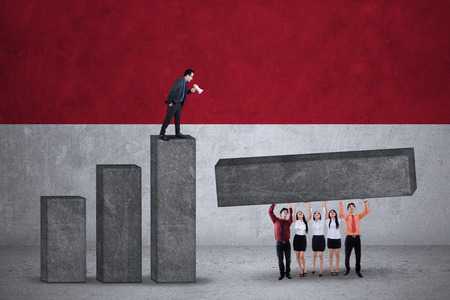 the indonesian flag: Group of young businesspeople build financial chart together with Indonesian flag backdrop Stock Photo