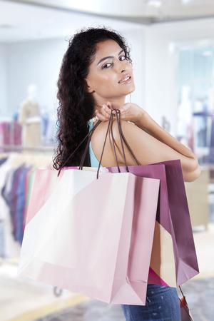 mujer alegre: Mujer india atractiva con el pelo rizado, con bolsas de compras en el centro comercial