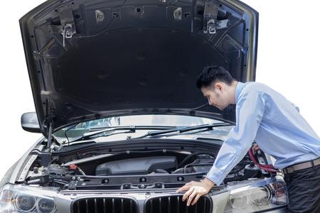 Afbeelding van de jonge ondernemer het controleren van de kapotte auto machine, geïsoleerd op een witte achtergrond