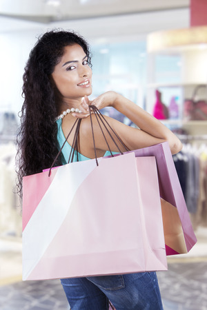 indonesian woman: Photo of young indian woman with long hair, carrying shopping bags in the shopping center Stock Photo