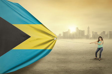 bahamas celebration: Photo of pretty woman with casual clothes, dragging a flag of Bahamas, shot outdoors