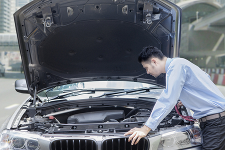 Photo of young businessman checking the broken car machine on the road