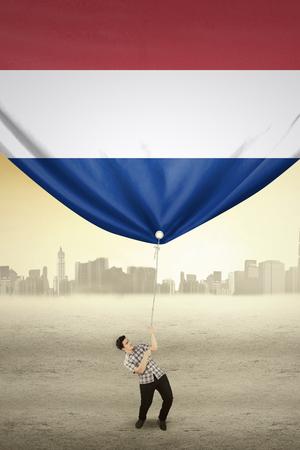 independencia: Hombre guapo con ropa casual, tirando de una bandera de los Pa�ses Bajos, dispar� al aire libre