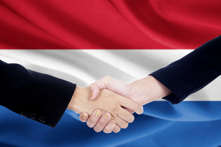 campaigning: Image of two people in business suit, shaking hands in front of Netherlands national flag Stock Photo