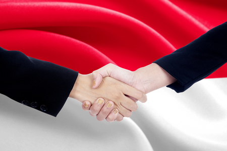 politicians: Closeup of two politicians shaking hands in front of Indonesia national flag Stock Photo