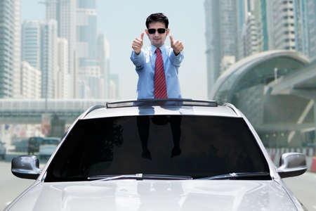business service: Portrait of successful person standing in the new car while showing thumbs up on the road Stock Photo