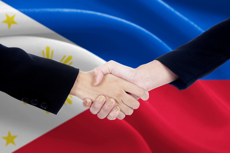 campaigning: Closeup of two businesspeople shaking hands in front of Philippines national flag