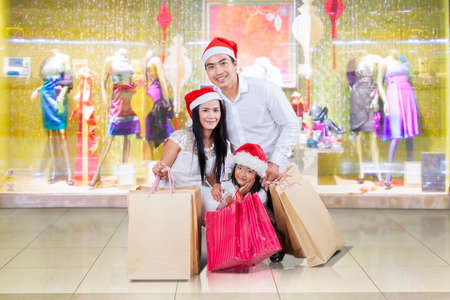 happy family shopping: Cheerful asian family kneeling at shopping center while wearing christmas hat and holding shopping bags