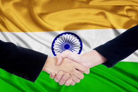 working woman: Photo of two entrepreneurs shaking hands in front of Indian national flag