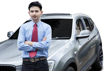 caras emociones: Foto del joven empresario de pie delante del nuevo coche de lujo, aislado en fondo blanco Foto de archivo