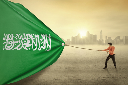 national identity: Image of young businessman pulling a flag of Saudi Arabia, shot outdoors Stock Photo