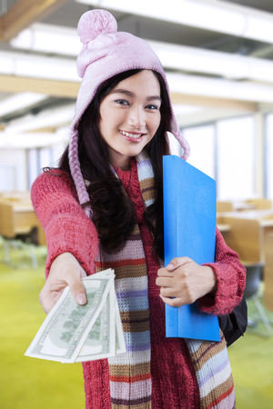 subsidy: Beautiful student in winter clothing, standing in the class and giving money dollars