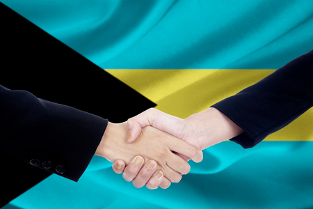 campaigning: Closeup of two people in formal suit, shaking hands in front of Bahamas flag