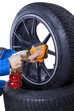 manos limpias: Imagen de manos mecánicas utilizando spray y paño para limpiar el polvo en el borde de los neumáticos