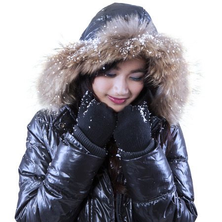fur hood: Pretty young girl wearing winter jacket with fur hood in studio, isolated on white background