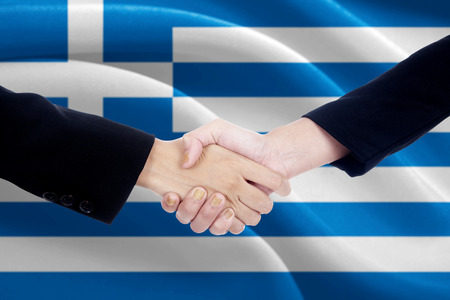 campaigning: Image of two politicians shaking hands in front of Greeces flag Stock Photo