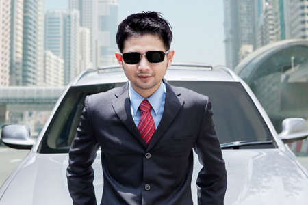 selling service smile: Photo of young businessman wearing formal suit and sunglasses in front of new car