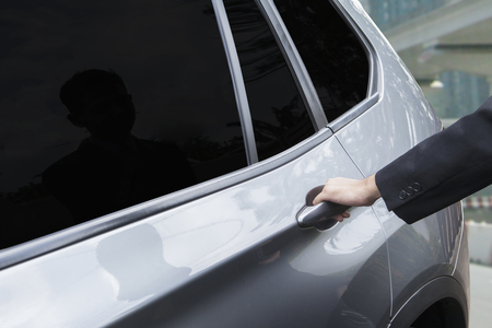 open car door: Image of businessman hands with formal wear, holding the new car handle