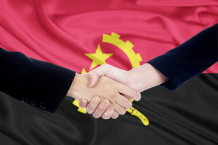 campaigning: Image of two businesspeople shaking hands in front of Angolas flag