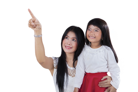woman pointing: Portrait of young asian mother with her daughter looking and pointing at copy space in the studio