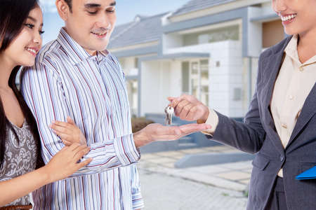 loans: Image of happy asian couple receive keys of their new home in front of the house