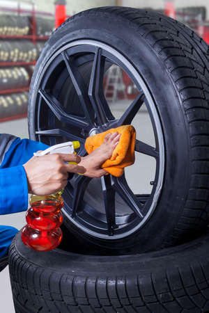tire repair shop: Image of mechanic hands holding spray and cloth to clean the dust on a tire rim Stock Photo