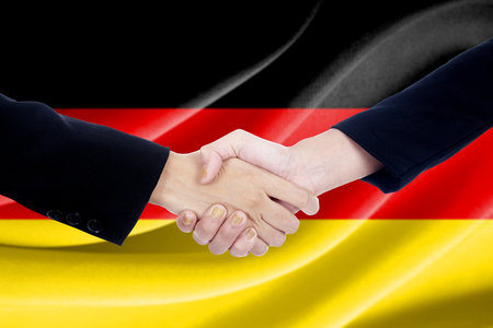 campaigning: Closeup of two people in formal suit, shaking hands in front of Germany flag Stock Photo
