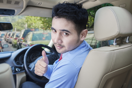 Portrait of young businessman driving a car while showing thumbs up on the traffic jam Stock Photo
