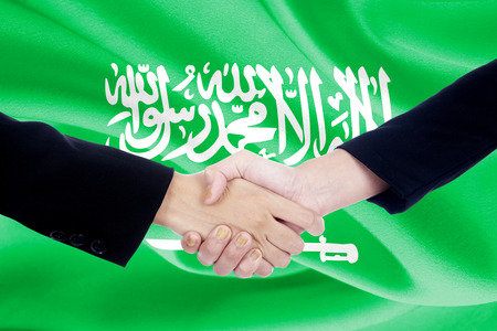 campaigning: Photo of two people shaking hands with flag of Saudi Arabia in the background
