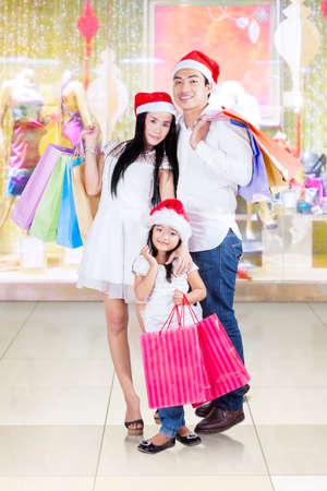 madre e hija: Imagen de la hermosa familia sonriendo a la cámara mientras llevaba bolsas de la compra y de pie en el centro comercial Foto de archivo