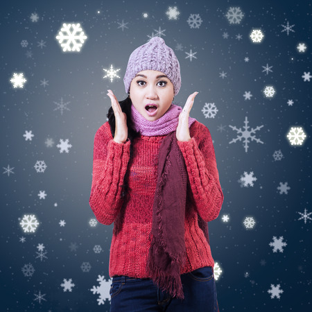 asian woman: Surprised beautiful girl with snowflakes background Stock Photo