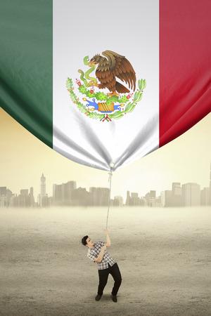 bandera mexicana: Foto de un joven con una cuerda para arrastrar una bandera de México, disparó al aire libre