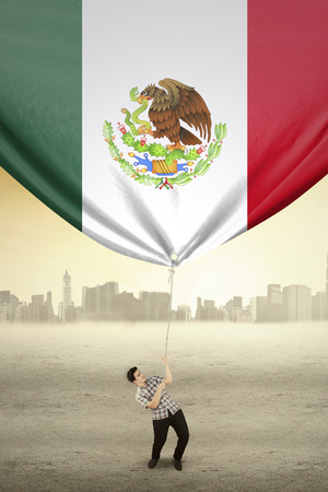 nationalities: Photo of a young person using a rope to drag a flag of Mexico, shot outdoors Stock Photo