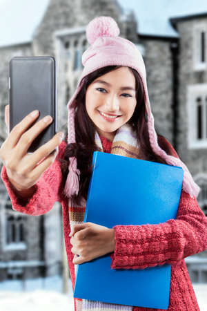 indian girl: Pretty teenage girl using a smartphone to take self portrait near the campus in winter day Stock Photo