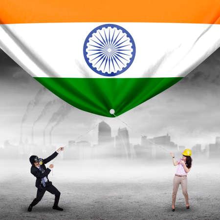 bandera de la india: Foto de dos j�venes empresarios que tiran de una gran bandera india, dispararon al aire libre Foto de archivo