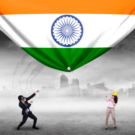 indian women: Photo of two young businesspeople pulling a big Indian flag, shot outdoors